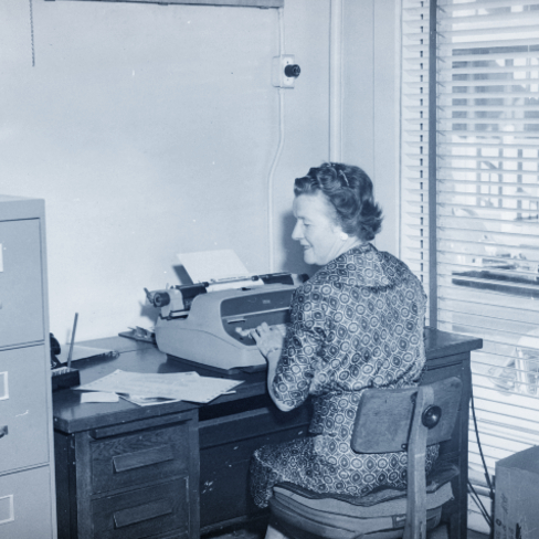 historic image of woman using typewriter circa 1960s